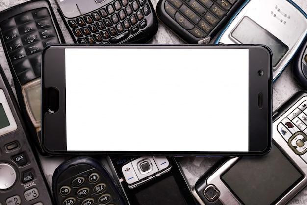 Un smartphone sur une pile de téléphones portables obsolètes.