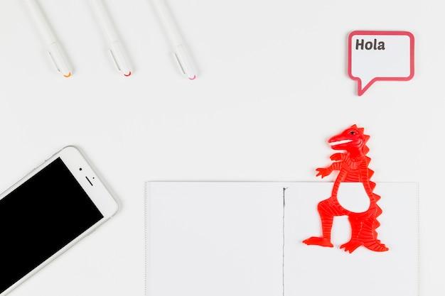 Smartphone près de stylo-feutre, papier, dinosaure jouet et cadre avec inscription hola