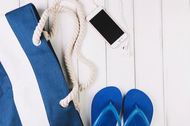 Smartphone près des tongs et sac