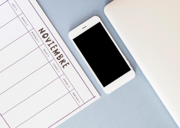 Smartphone proche du calendrier et du papier