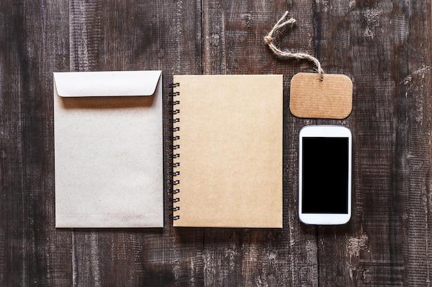Smartphone sur des sacs pour ordinateur portable et calicot sur une vieille table en bois