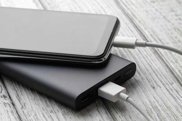 Le smartphone se charge depuis une batterie externe avec un câble