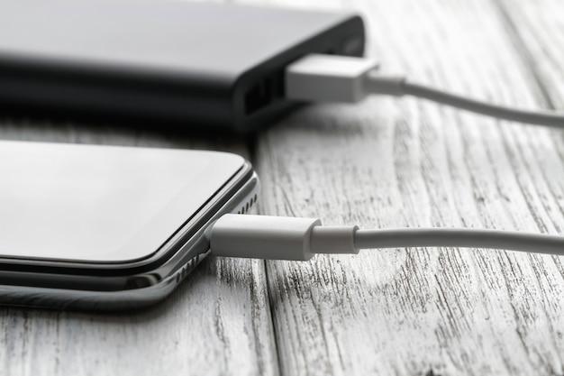 Le smartphone se charge à partir d'une batterie externe avec un câble