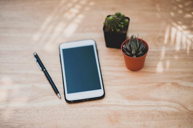 Smartphone sujet flou sur table en bois travaillant à la maison concept