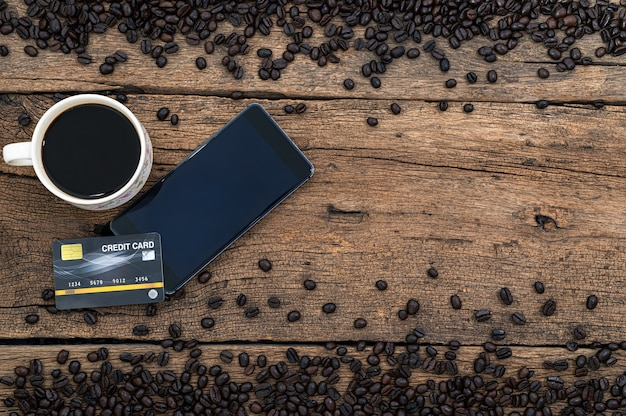 Smartphone, la tasse de café et les grains de café sont sur la vue de dessus du bureau