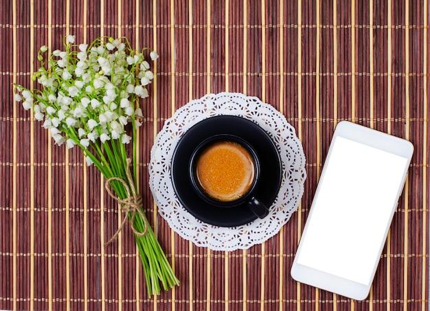 Smartphone, tasse de café noire avec du lait sur une soucoupe et un bouquet de muguets sur la table