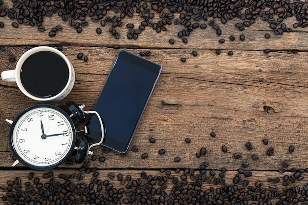 Un smartphone, une tasse, du café, une horloge et des grains de café sur le bureau, vue de dessus.