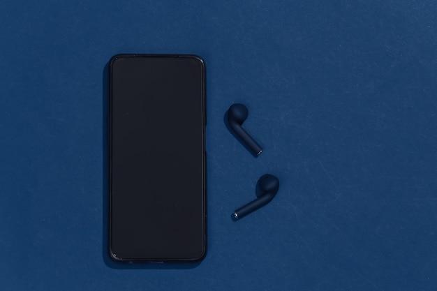 Smartphone et véritables écouteurs ou écouteurs bluetooth sans fil sur fond bleu classique.