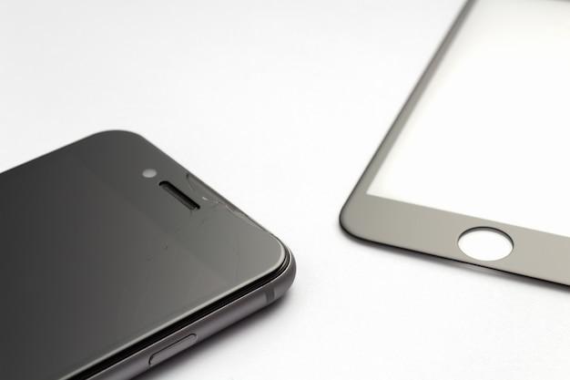 Smartphone avec verre de protection fissuré sur fond blanc.