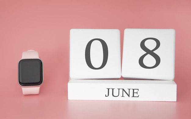 Smartwatch avec calendrier cube et date 08 juin sur table rose.