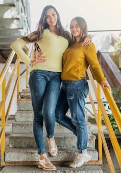 Smile amis entiers posant dans les escaliers
