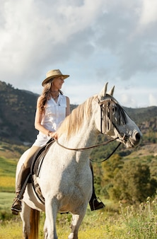 Smiley agricultrice équitation dans la nature