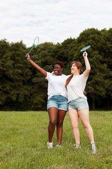 Smiley amies à l'extérieur tenant des raquettes