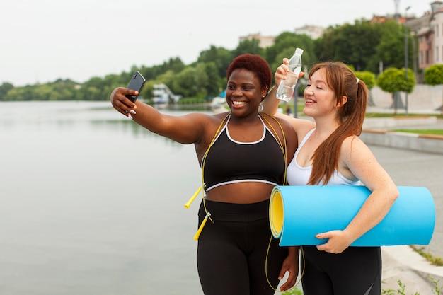 Smiley amies prenant selfie tout en faisant de l'exercice à l'extérieur