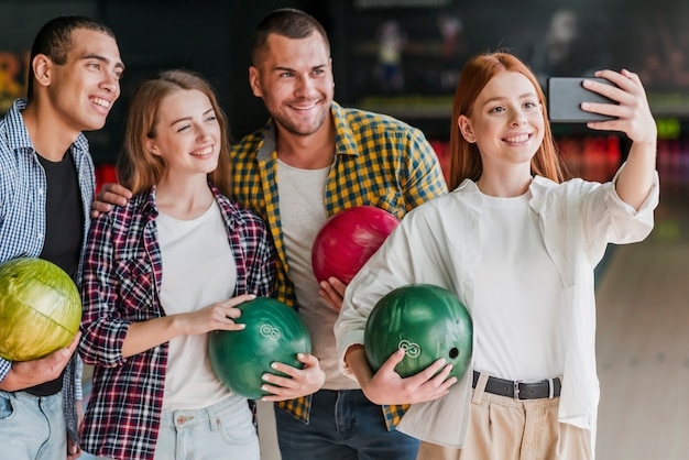 Smiley amis posant dans un club de bowling