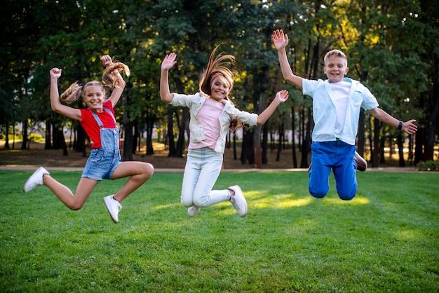 Smiley amis sautant à regarder la caméra