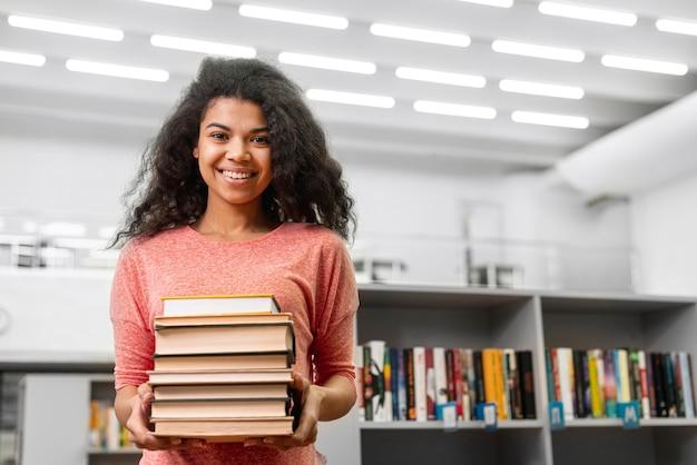 Smiley angle faible avec pile de livres
