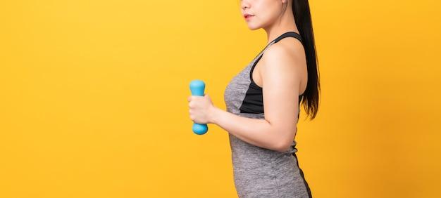 Smiley asian woman wearing sportswear pompage des muscles avec haltère bleu sur orange clair.