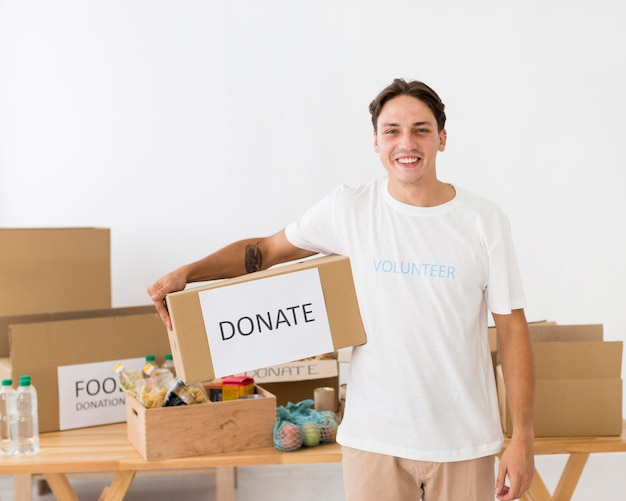 Smiley bénévole tenant une boîte de don