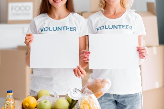 Smiley bénévoles féminins posant avec des pancartes vierges et des dons de nourriture