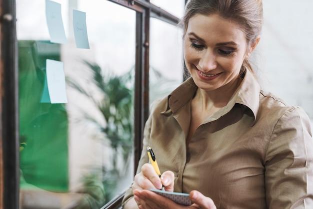 Smiley businesswoman prendre des notes lors d'une réunion