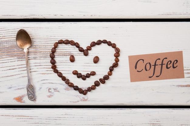 Smiley coeur fait de grains de café et cuillère à café sur bois. concept d'amour de café. vue de dessus à plat.