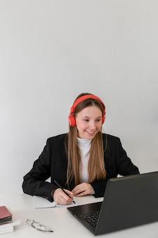 Smiley coup moyen femme travaillant avec ordinateur portable