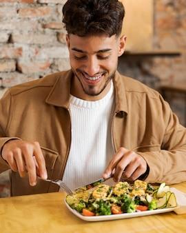 Smiley coup moyen homme mangeant de la nourriture