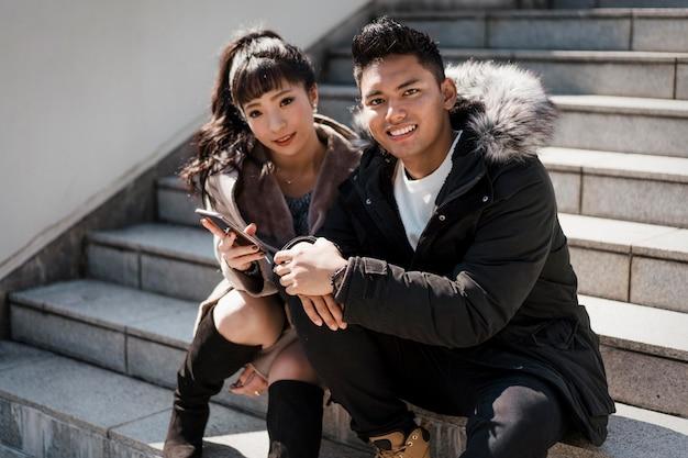 Smiley couple assis dans les escaliers avec smartphone