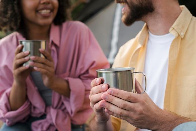 Smiley couple ayant des boissons chaudes en camping en plein air
