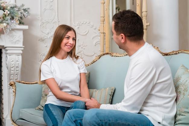 Smiley couple main dans la main sur le canapé