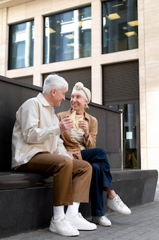 Smiley couple de personnes âgées à l'extérieur appréciant un sandwich ensemble