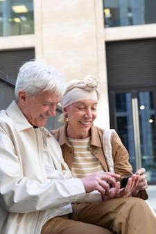 Smiley couple plus âgé utilisant un smartphone ensemble à l'extérieur
