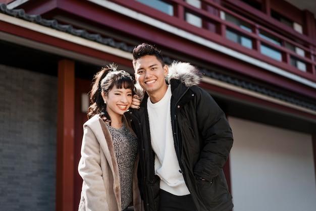 Smiley couple posant ensemble à l'extérieur