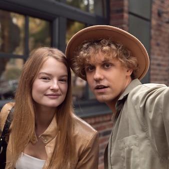 Smiley couple prenant selfie à l'extérieur