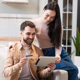 Smiley couple shopping en ligne sur tablette