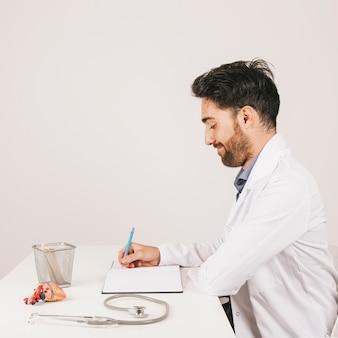 Smiley doctor assis à son bureau et écrit