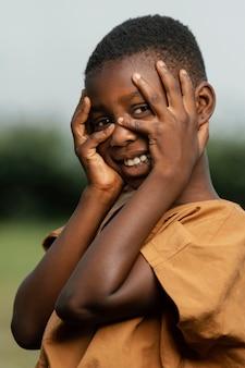 Smiley enfant africain tenant les mains sur le visage