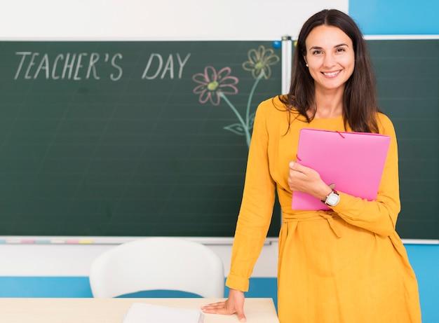 Smiley enseignant posant en classe avec espace copie