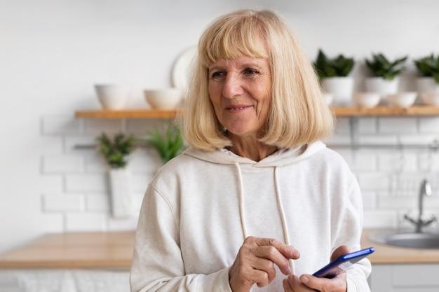 Smiley femme âgée à l'aide de smartphone à la maison