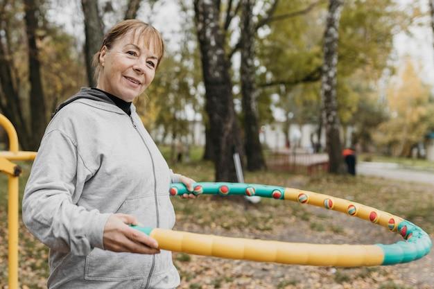 Smiley femme âgée à l'extérieur travaillant avec de l'équipement
