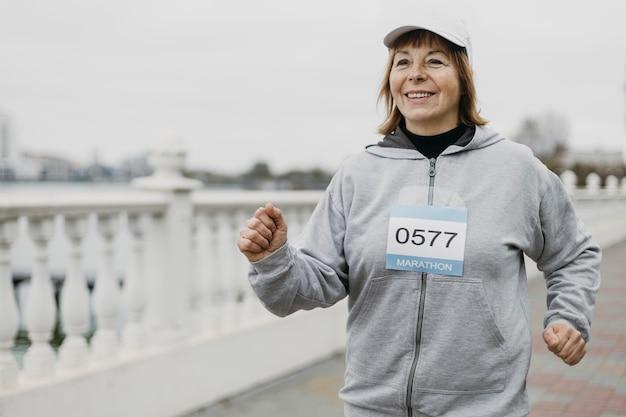 Smiley femme âgée jogging à l'extérieur avec espace copie