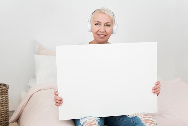 Smiley femme âgée portant des écouteurs et tenant une pancarte vierge dans son lit