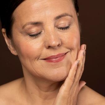 Smiley femme âgée posant avec du maquillage sur