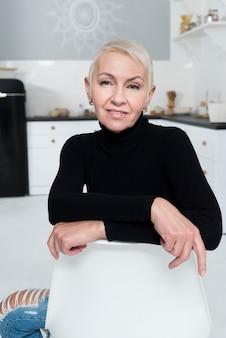 Smiley femme âgée souriante et posant dans la cuisine