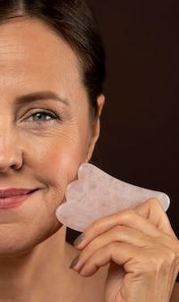 Smiley femme aînée à l'aide de sculpteur de visage de quartz rose avec copie espace