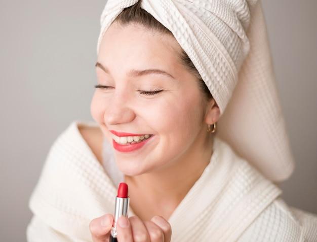 Smiley femme appliquant le rouge à lèvres