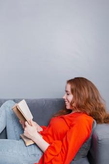 Smiley femme appréciant lecture à la maison