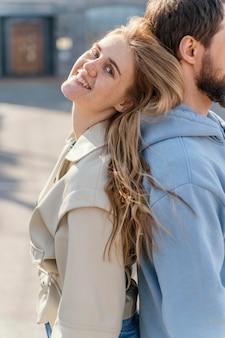 Smiley femme appuyée contre un homme à l'extérieur