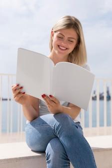 Smiley femme assise à l'extérieur et livre de lecture